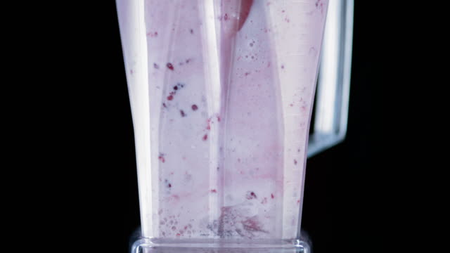 slo mo mixing a strawberry milkshake in a blender - smoothie stock videos & royalty-free footage