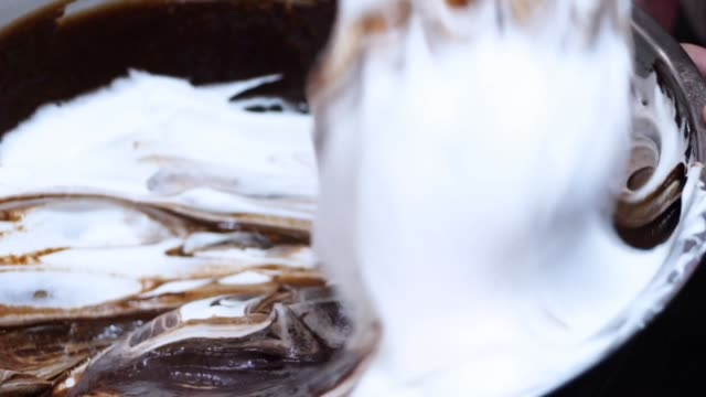 mixing chocolate butter cream in big bowl, processing cupcakes. - messy stock videos & royalty-free footage