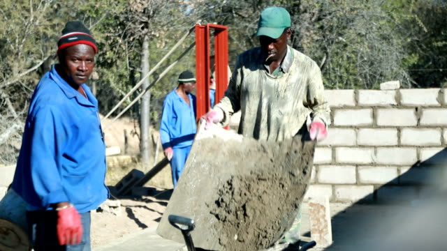 ha cu mixing concrete with a shovel in a wheelbarrow cape town is located on the western coast and isthe second largest city in south africa as it is... - wheelbarrow stock videos & royalty-free footage