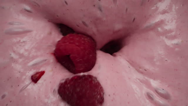 mixing frozen raspberries into a smoothie - smoothie stock videos & royalty-free footage