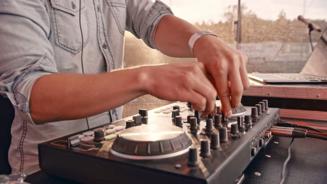 dj mixing music on the console in sunshine - knob stock videos & royalty-free footage