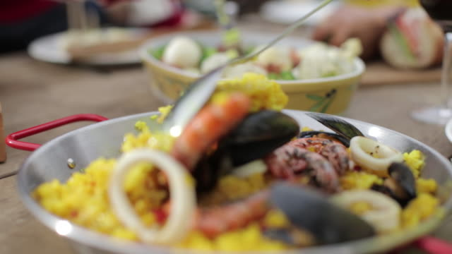 mixing paella at the table using spoon - food state stock videos and b-roll footage
