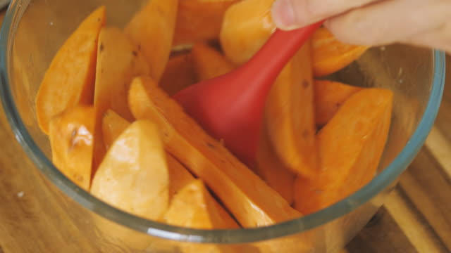 mixing sweet potato wedges with olive oil - sweet potato stock videos & royalty-free footage