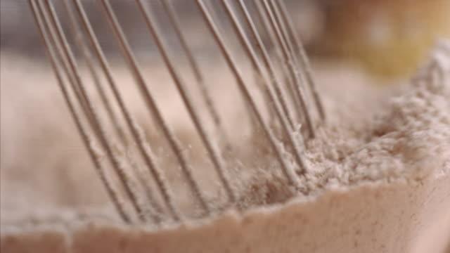 stockvideo's en b-roll-footage met mixing whisking flour and dry ingredients in mixing bowl banana pancake recipe v2 - volkorentarwe