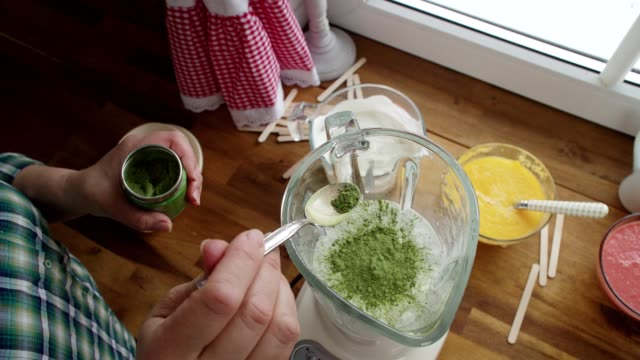 mixing yoghurt and green tea in a blender for preparing ice cream on stick - green tea ice cream stock videos and b-roll footage