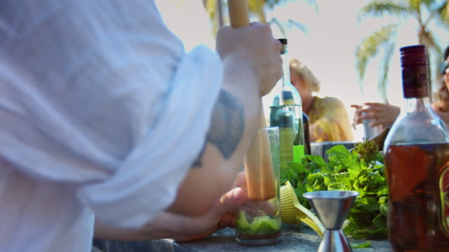 Mixologist Crushing Lime Wedges at Outdoor Pool Party