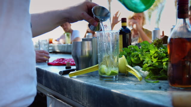stockvideo's en b-roll-footage met mixologist maken van dranken op outdoor pool party - cocktail