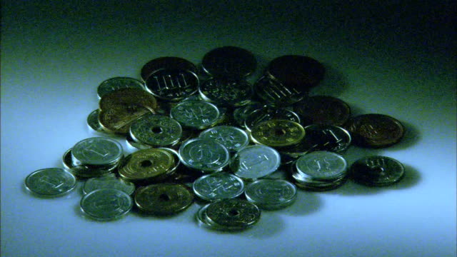 Mixture of Japanese coins scattered carelessly on a flat surface in a dark place