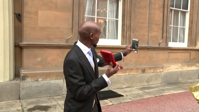 London Buckingham Palace EXT Sir Mo Farah filming himself on his phone with knighthood medal Medal in box