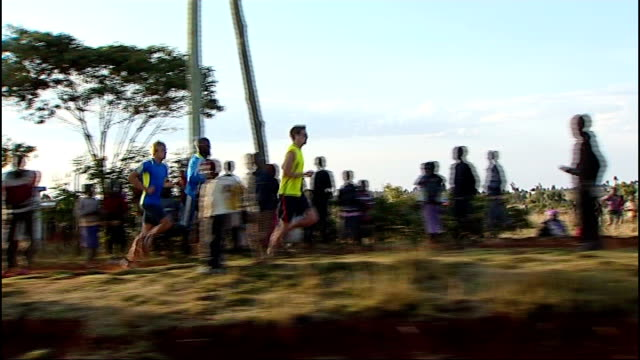 Mo Farah training in the Great Rift Valley Farah and others jogging during training session Legs of runners along and past Farah and other distance...