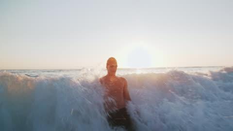 ws slo mo young man walking into the sea at sunset - mod bildbanksvideor och videomaterial från bakom kulisserna