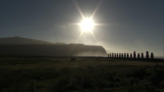 moai statues on ahu platform on rocky coast at sunrise, easter island - maui stock videos & royalty-free footage
