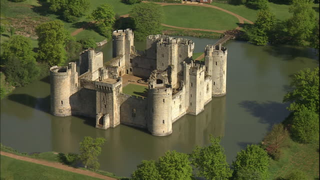 a moat surrounds bodiam castle in east sussex, england. - schlossgebäude stock-videos und b-roll-filmmaterial