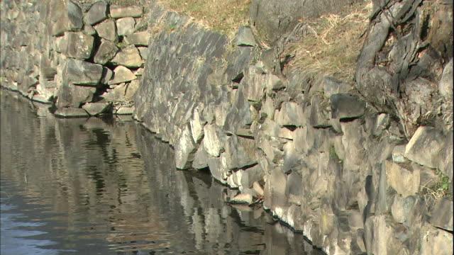 moat water reflects stone walls at matsumoto castle at nagano. - moat stock videos & royalty-free footage