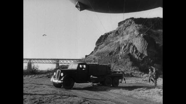 b/w mobile balloon squadron deploying helium barrage balloons around the forth bridge, balloons at high and low altitude over the bridge, and balloon's shadow on hillside / rosyth, scotland, united kingdom - fluss firth of forth stock-videos und b-roll-filmmaterial