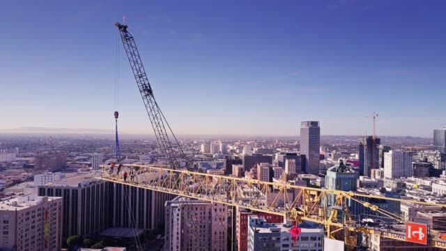 mobile crane hooking onto boom of tower crane being dismantled - crane stock videos & royalty-free footage