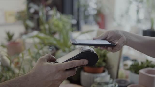 vídeos de stock e filmes b-roll de mobile payment at the small retail shop - pagar