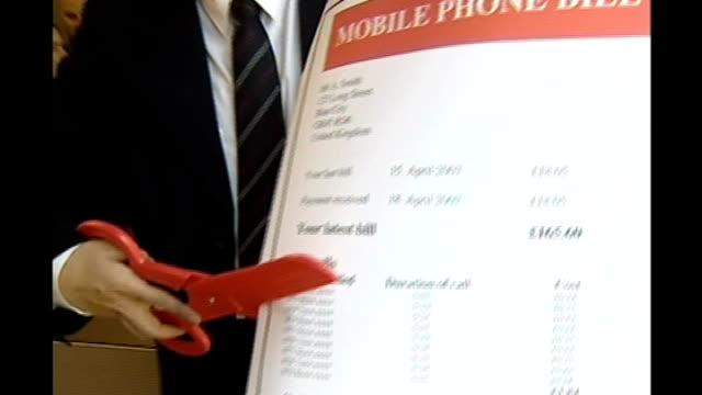 mobile phone companies to reduce cost of calls in europe location unknown int unidentified man cutting oversized mobile phone bill with giant red... - cut video transition stock videos & royalty-free footage