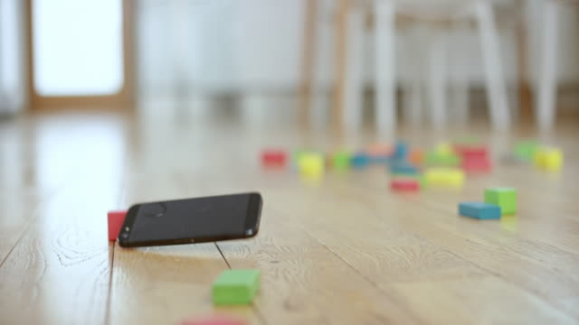 vídeos de stock e filmes b-roll de slo mo mobile phone falling on the floor covered with wooden toy blocks - gravity