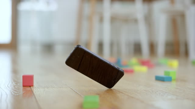 mobile phone falling onto the floor covered with toy blocks - wooden floor stock videos & royalty-free footage