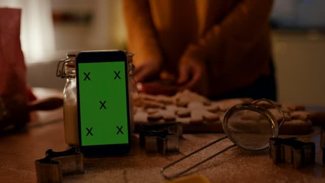 vídeos de stock, filmes e b-roll de celular no balcão da cozinha enquanto mulher colocando biscoitos de gengibre em recipiente no fundo - modelo web