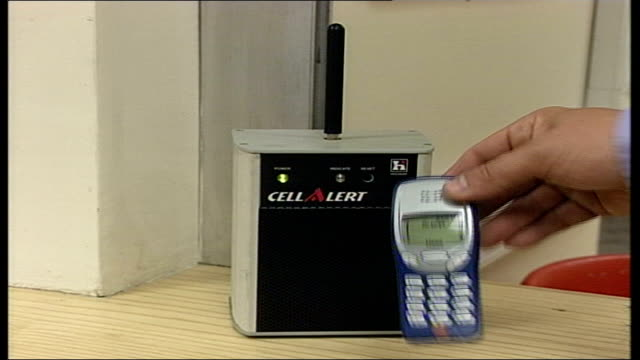 mobile phone radiation levels to be published: cell alert device; itn england: london: int cell alert' device as placed on table / mobile phone held... - t cell stock videos & royalty-free footage