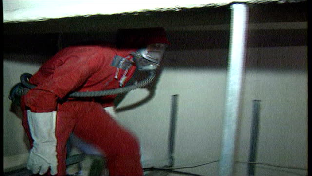 five year study planned file / tx location unknown int workers wearing protective suits and masks removing asbestos from roof cavity to - asbest stock-videos und b-roll-filmmaterial