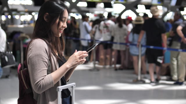 SEA: Mobile phone use, Asian woman using phone at airport