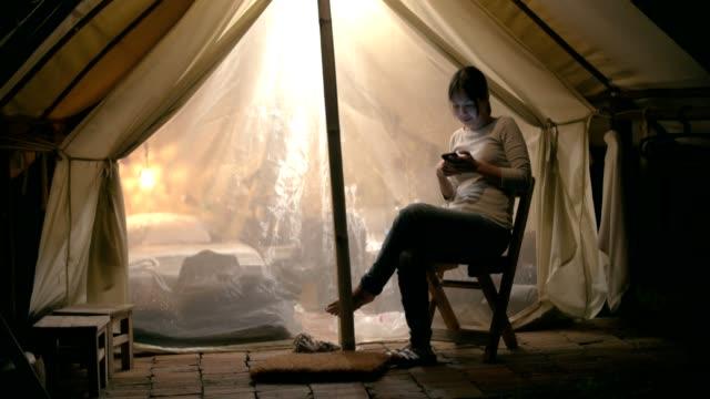 海: 携帯電話を使用してください、魅力的な女性は夜に携帯電話を使用してください。 - テント点の映像素材/bロール