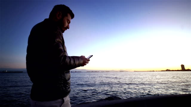 mobile phone use man and istanbul sunset sea view - 4k - distillery still stock videos and b-roll footage