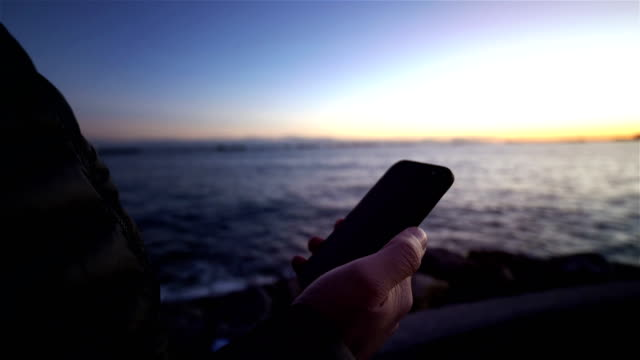 mobile phone use man and sunset sea view - distillery still stock videos & royalty-free footage