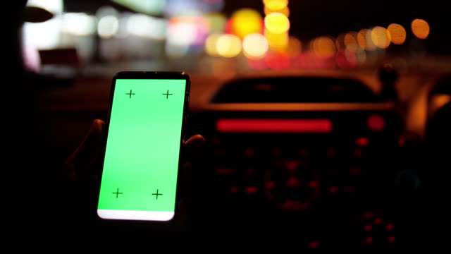 mobile phone with green screen at night and bokeh circle light - car chroma key stock videos & royalty-free footage