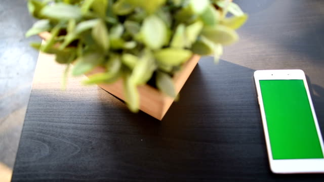 mobile phone with green screen laying on wooden table - template stock videos & royalty-free footage