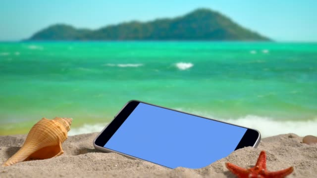 mobile phone with open screen on the beach at sunset. - conch stock videos & royalty-free footage