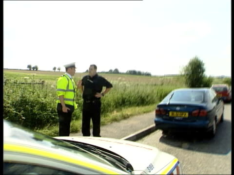 drivers banned from using handheld phones itn england hampshire police officer driving car along road track ms police officer talking to driver... - hampshire england stock videos & royalty-free footage