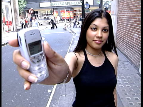 Growth in sale of ringtones ITN ENGLAND London Young Asian female holds up Nokia mobile phone playing Ms Dynamite ringtone SOT LMS White male...