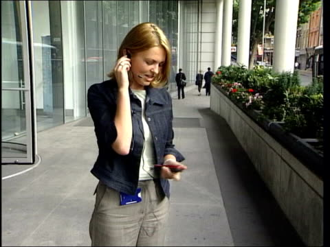 new report into safety issues; cf tape no longer available itn england: london: gir: ext mss woman speaking on mobile phone using hands-free... - headset stock videos & royalty-free footage