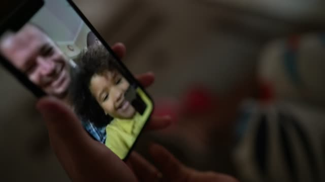 Mobile screen on a family video chat at home