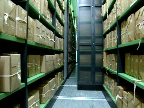 stockvideo's en b-roll-footage met mobile shelf full of box files is rolled aside in the vault of a public records office; 1999 - bbc archives