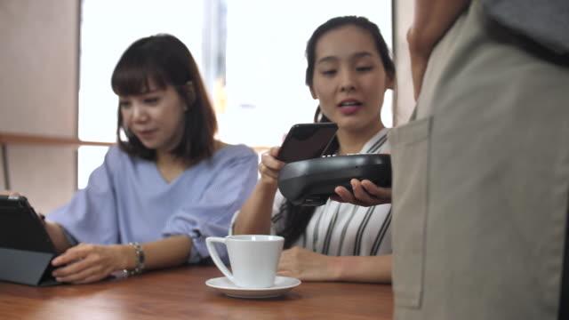 カフェで携帯/非接触型決済 - 支払い点の映像素材/bロール