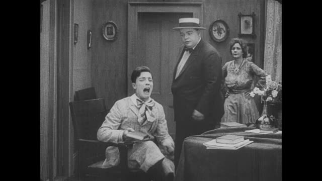 1917 mocking man (buster keaton) gets thrown into chair by frustrated man (fatty arbuckle) who kick's keaton's feet off of coffee table - マナー点の映像素材/bロール