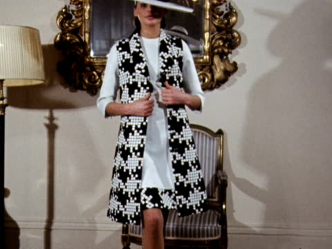 a model admires herself in a mirror and then turns to the camera wearing a black and white patterned sleeveless coat and a dress designed by mattli... - admiration stock videos & royalty-free footage