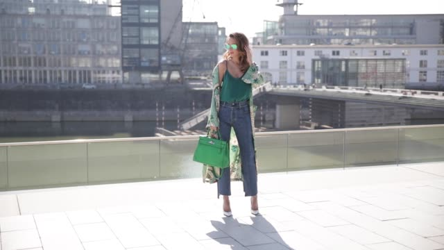 vídeos de stock, filmes e b-roll de model and fashion blogger alexandra lapp wearing wearing a green flower printed kimono from zara, a green tank top in silk, blue jeans from vetements... - blusa roupa