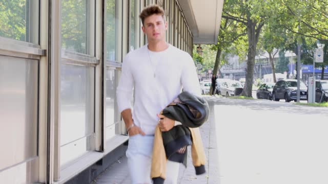 model and influencer fabian arnold wearing a white pullover by zara, a camel colored and olive green colored jacket by sayasaya, a black belt by... - メルセデスベンツファッションウィーク点の映像素材/bロール