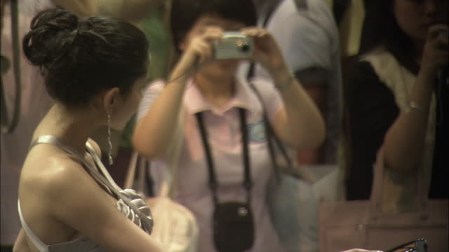 montage model and spectators at beijing auto show, beijing, china - millionär stock-videos und b-roll-filmmaterial