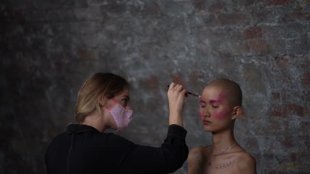 a model backstage and makeup artist wears a face mask ppe ahead of the lula laora show during lfw september 2020 at studio z brixton on september 22... - human head stock videos & royalty-free footage