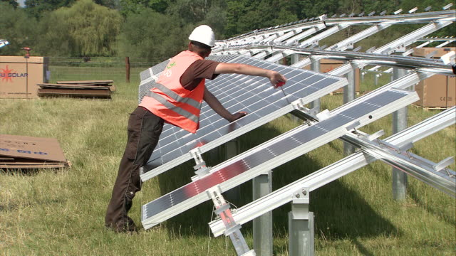 MS Model checking and tightening fittings on line of solar panels / Howbery, Oxfordshire, United Kingdom