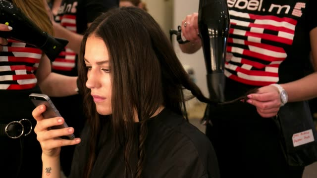 model checks her phone whilst having her hair done backstage at the saint james fashion show during london fashion week men's on june 9, 2018 in... - fashion show stock videos & royalty-free footage