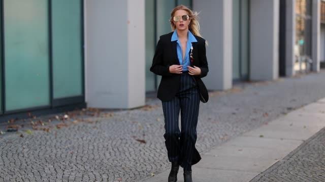Model Cheyenne Tulsa is seen wearing black vintage blazer blue Calvin Klein button shirt striped flared pants with slit Kiomoi x CLO sunglasses Linda...