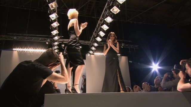 ms model clapping on catwalk at end of fashion show/ designer arriving, taking bow as camera flash goes off, and walking away/ london, england - fashion show stock videos & royalty-free footage